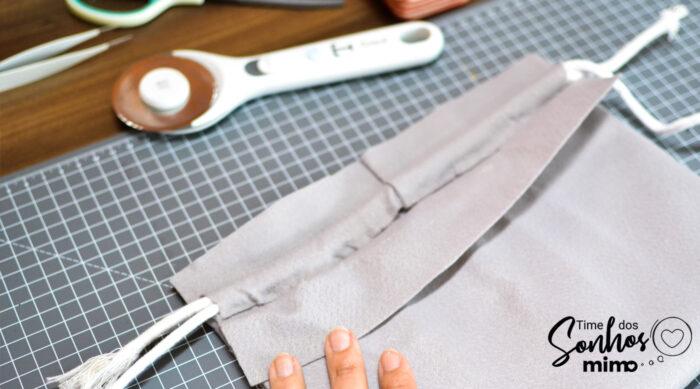 Passe os cordões em uma das partes de cima que você fez o corte e cole