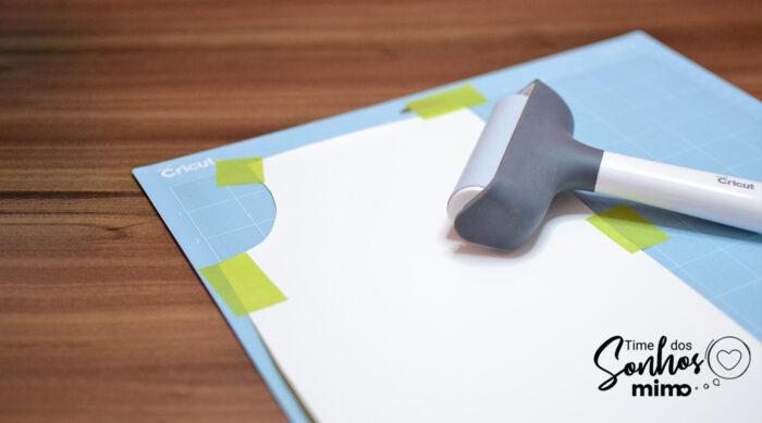 Se sua base estiver com pouca cola ou se seu transfer insistir em enrolar novamente, use alguma ferramenta para passar por cima (o rolinho da Cricut é perfeito pra isso) e use pedaços de fita crepe nas pontas